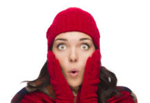 Expressive Mixed Race Woman Wearing Winter Hat and Gloves Isolated on White Background.