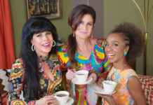 Giggling ladies holding teacups in 1960s style