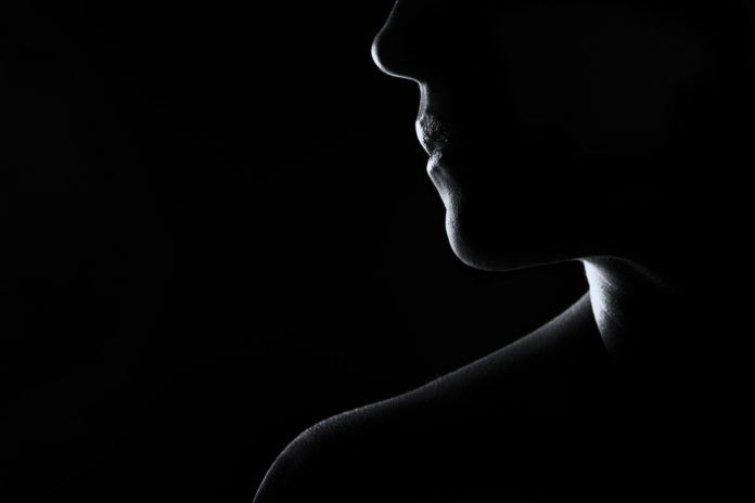 Silhouette of a woman face in black and white with rim lighting